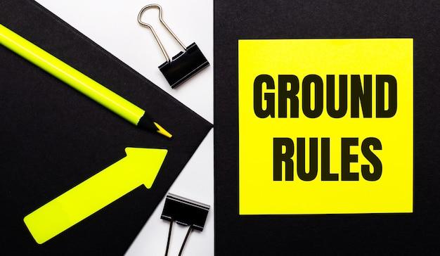 Sobre un fondo negro, un lápiz amarillo brillante y una flecha y una hoja de papel amarilla con el texto reglas de base