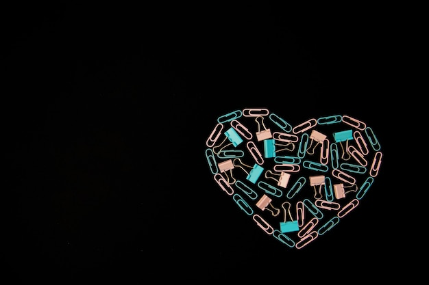 Sobre un fondo negro, los sujetapapeles en forma de corazón son de color azul y rosa. material de oficina. fondo y textura. el concepto de san valentín.