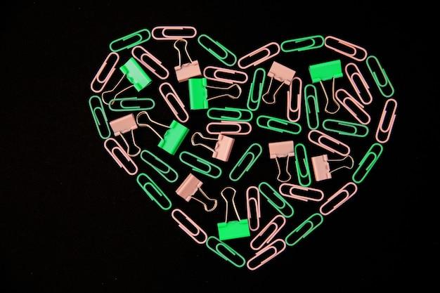 Sobre un fondo negro, los sujetapapeles en forma de corazón son de color verde y rosa. material de oficina. fondo y textura. el concepto de san valentín.