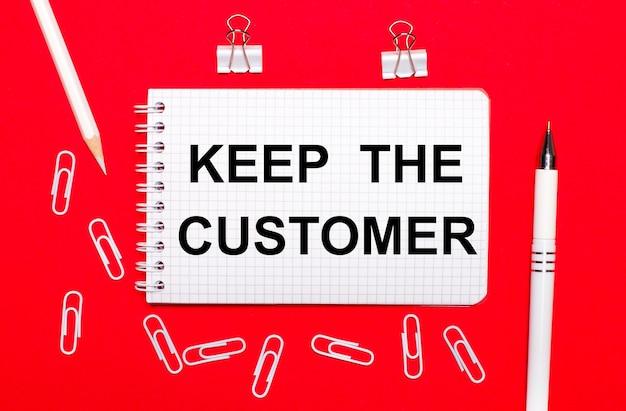 Sobre un fondo rojo, un bolígrafo blanco, sujetapapeles blancos, un lápiz blanco y un cuaderno con el texto mantener al cliente