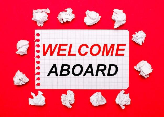 Sobre un fondo rojo brillante, hojas de papel blancas arrugadas y una hoja de papel con el texto bienvenido al extranjero