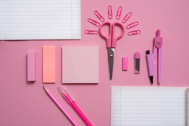Sobre un fondo rosa, accesorios escolares y una pluma, lápices de colores, un par de brújulas.