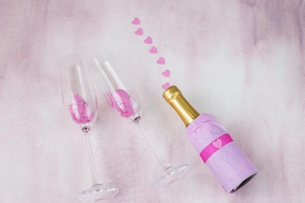Sobre un fondo rosa una botella de champán y corazones rosados - despedida de soltera