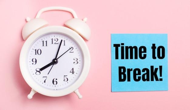 Sobre un fondo rosa claro, un despertador blanco y una hoja de papel azul con el texto hora de romper