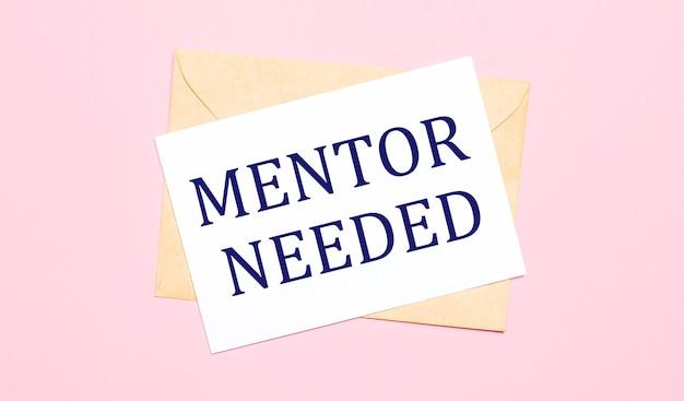 Sobre un fondo rosa claro: un sobre artesanal. tiene una hoja de papel blanca que dice mentor necesario.