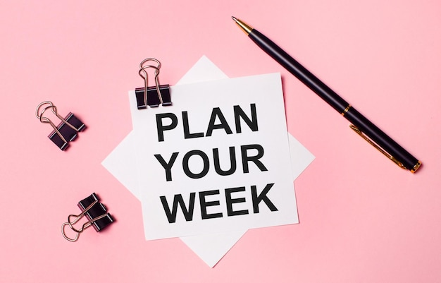 Sobre un fondo rosa claro, sujetapapeles negros, bolígrafo negro y papel de notas blanco con las palabras planifique su semana. endecha plana