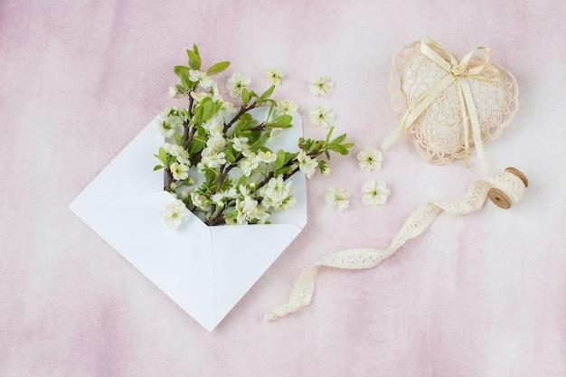 Sobre un fondo rosa en un sobre de ramas de cerezo, un corazón de encaje y cinta de encaje