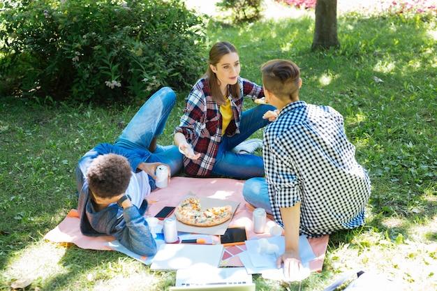 Sobre la hierba. estudiantes con estilo moderno que se sienten descansados y aliviados mientras están sentados en el césped mientras hacen un picnic