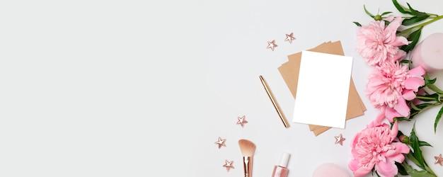 Sobre de kraft con una hoja blanca de papel, flores de peonías, velas rosadas.