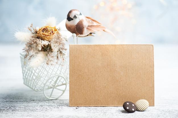 Sobre kraft y ramo de flores secas en bicicleta decorativa con pequeño pájaro marrón sobre la mesa. tarjeta de felicitación para boda o vacaciones en tonos naturales.