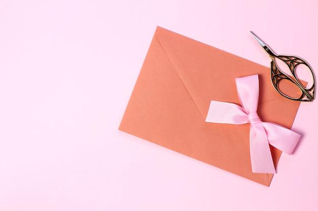 Un sobre con un lazo rosa sobre un fondo rosa pastel. estilo plano laico.