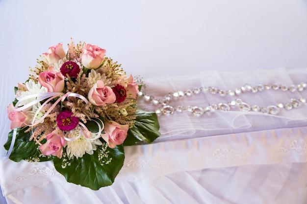 Sobre un mantel blanco un ramo de boda para una ceremonia de boda