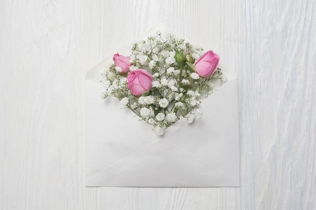 Sobre de maqueta con flores y una carta, tarjeta de felicitación para el día de san valentín o una boda con lugar para el texto