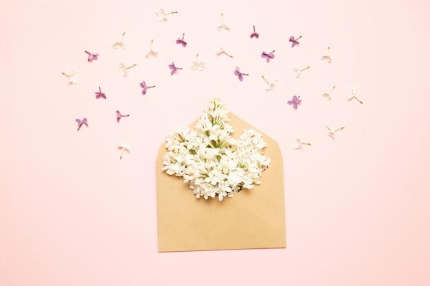 Sobre de la maqueta con ramas de color lila sobre un fondo rosa