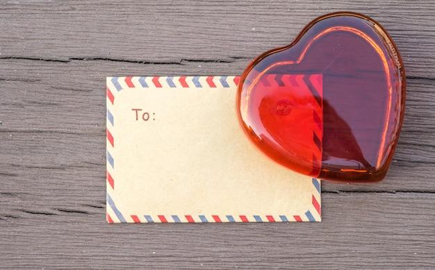 Sobre marrón del primer con el vidrio rojo en forma del corazón en la tabla de madera vieja