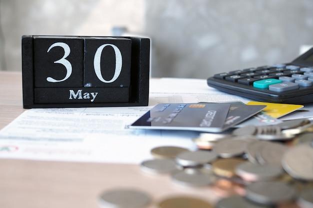Sobre la mesa con facturas, tarjetas de crédito, calculadoras, monedas, calendario.
