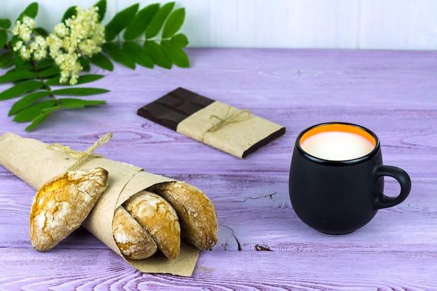 Sobre la mesa, flores de primavera, una taza de leche y galletas caseras y chocolate.
