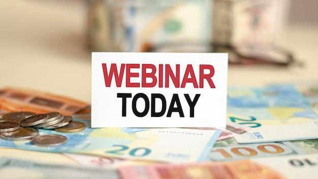 Sobre la mesa hay billetes, un paquete de dólares y un cartel en el que está escrito: webinar hoy. concepto de finanzas y economía.
