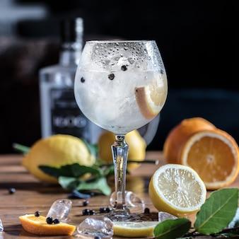 Sobre la mesa hay un cóctel frío de limón con rodajas de hielo con limones y naranjas enteros.