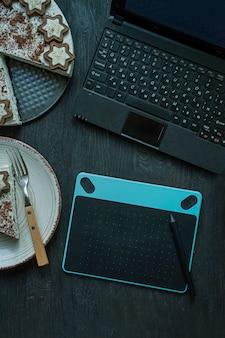 Sobre la mesa hay una computadora portátil, una tableta gráfica y una taza de café.