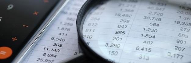 Sobre la mesa hay documentos con estados financieros encima de una lupa. concepto de desarrollo de pequeñas y medianas empresas.