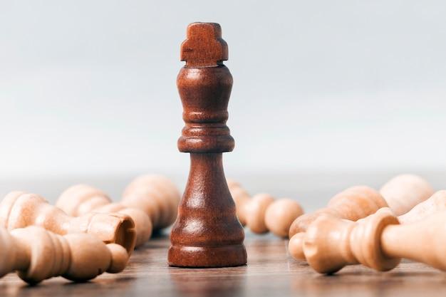 Sobre la mesa hay una figura de un rey del ajedrez negro. alrededor de los cuales yacen los peones. concepto de éxito empresarial