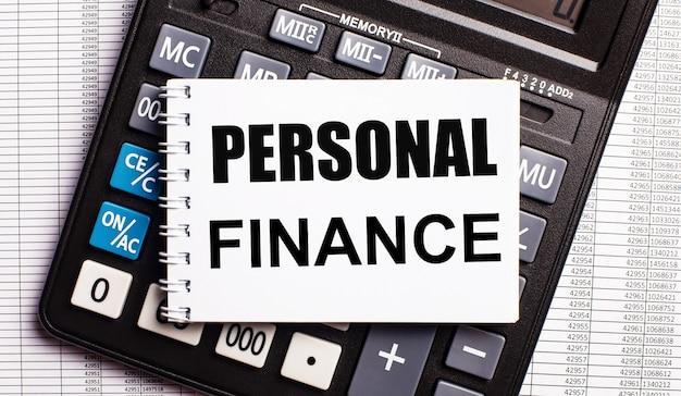 Sobre la mesa hay informes, una calculadora y una tarjeta con las palabras finanzas personales. concepto de negocio