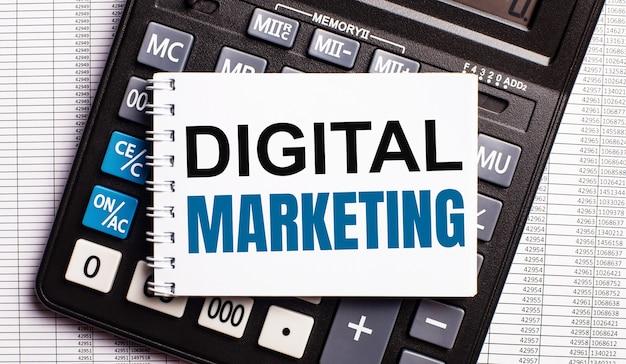 Sobre la mesa hay informes, una calculadora y una tarjeta con las palabras marketing digital