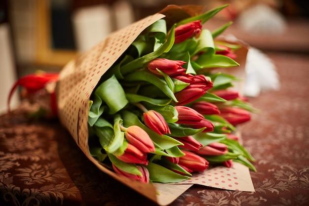 Sobre la mesa hay un ramo de tulipanes.