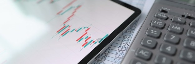 Sobre la mesa hay una tableta con calculadora de gráficos comerciales y documentos con informes pequeños y