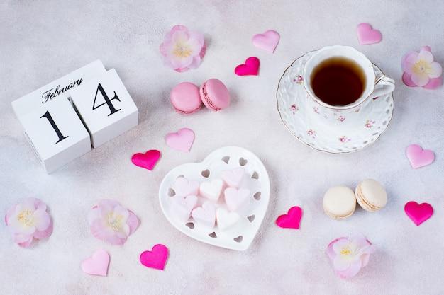 Sobre la mesa hay una taza de té, flores rosas, malvaviscos en forma de corazón, corazones de satén, macarrones y una fecha calendario del 14 de febrero