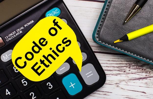 Sobre una mesa de madera clara, hay una calculadora, un cuaderno, un bolígrafo, un lápiz amarillo y una tarjeta amarilla con el texto código de ética. concepto de negocio.