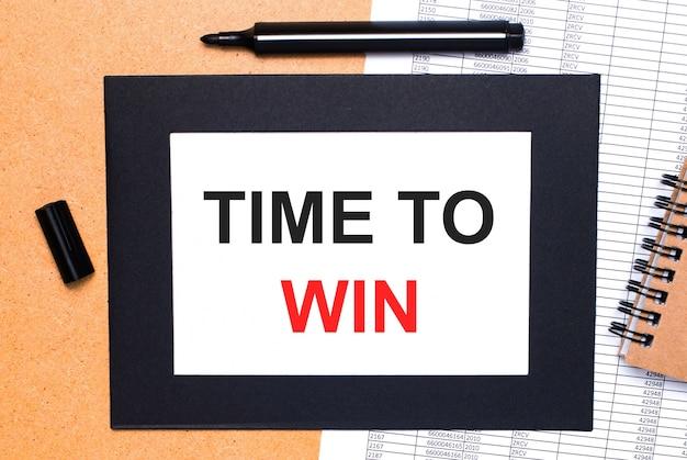 Sobre una mesa de madera, hay un rotulador negro abierto, un bloc de notas marrón y una hoja de papel en un marco negro con el texto time to win. vista desde arriba.