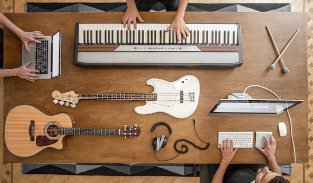 Sobre una mesa de madera hay teclas musicales, guitarra acústica, bajo, mezclador de sonido, auriculares, computadora y baquetas.