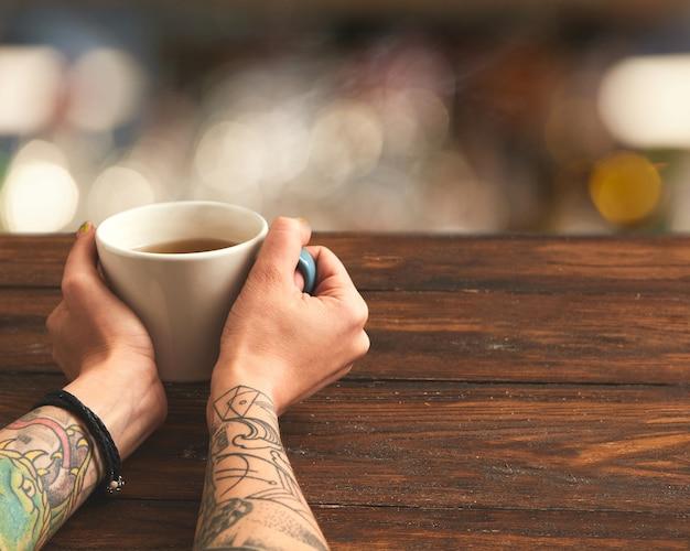 Sobre una mesa de madera marrón, una taza de té verde en manos femeninas