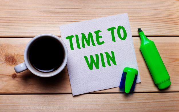 Sobre una mesa de madera, una taza de café, un rotulador verde y una servilleta con el texto hora de ganar