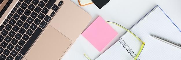 Sobre la mesa, portátil, smartphone, gafas, bolígrafo y bloc de notas.