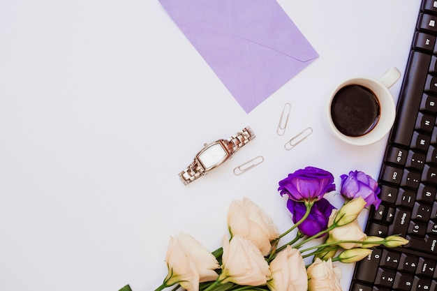 Sobre morado; reloj de pulsera; clip de papel; taza de café; teclado y flores de eustoma sobre fondo blanco.