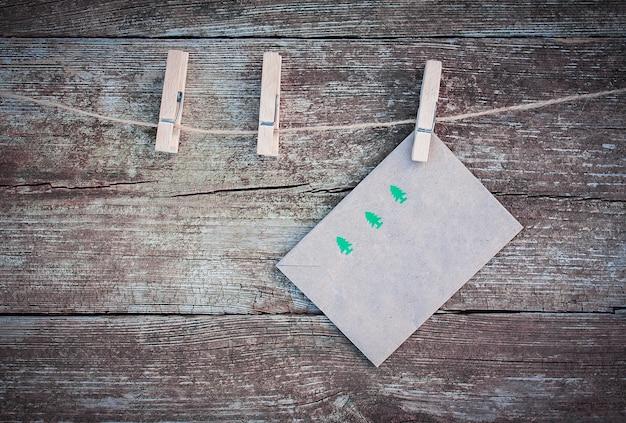 Sobre de navidad con imagen de abetos verdes colgando de una cuerda con pinzas para la ropa