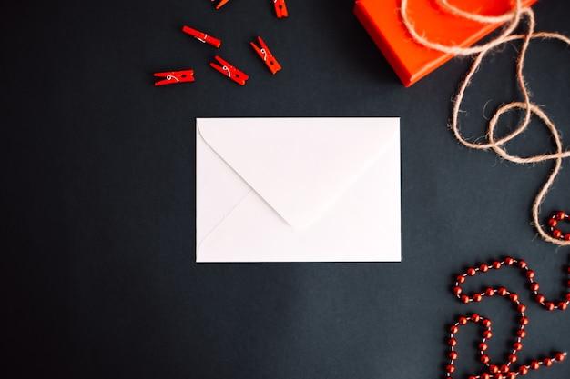 Sobre de papel blanco con caja de regalo sobre fondo negro. concepto del día de san valentín