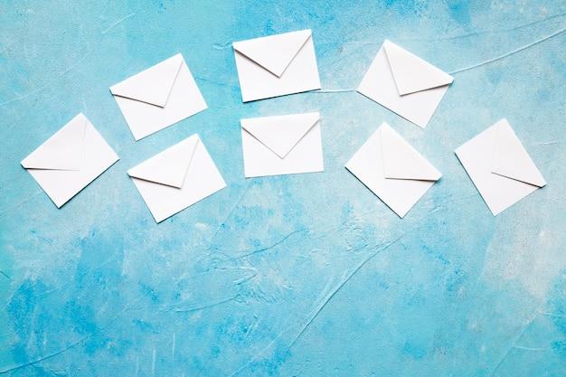Sobre de papel blanco de iconos de mensaje sobre fondo azul con textura