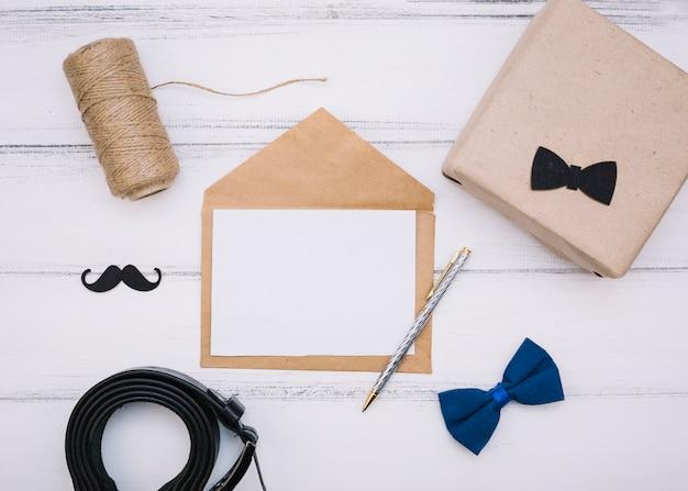Sobre con papel cerca de caja, hilos y correa de piel.