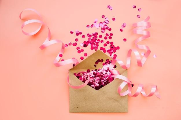 Sobre de papel con confeti rosa y cintas