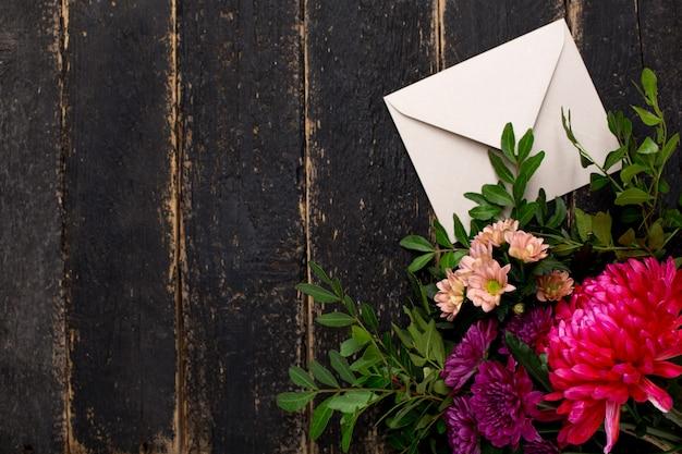 Sobre con un ramo de flores en una madera oscura vintage.
