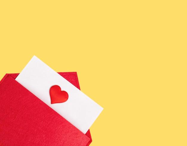Sobre rojo abierto con una hoja de papel con un corazón sobre un fondo amarillo con copyspace. día de san valentín