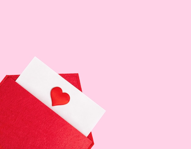 Sobre rojo abierto con una hoja de papel con un corazón sobre un fondo rosa con copyspace. día de san valentín