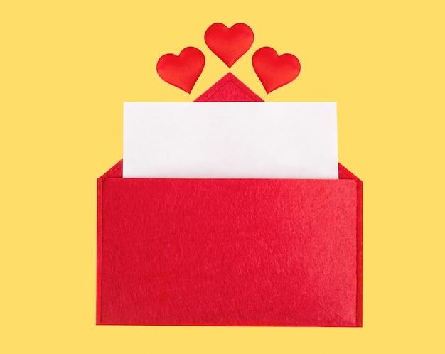 Sobre rojo abierto con una hoja de papel con corazones sobre un fondo amarillo. día de san valentín