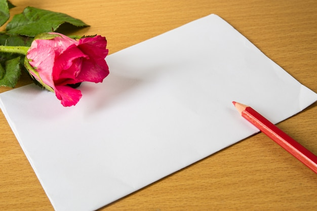 Sobre rojo con almohada de corazón de forma sobre texto amor y rosa, hoja de papel y sobre fondo de madera