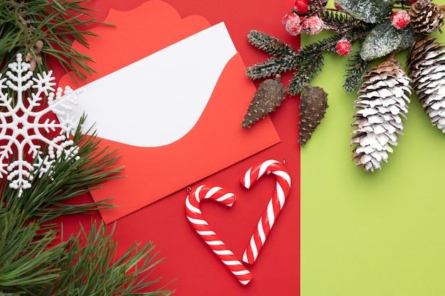 Sobre rojo navideño con espacio para texto sobre un fondo rojo y verde con copos de nieve navideños y caramelos