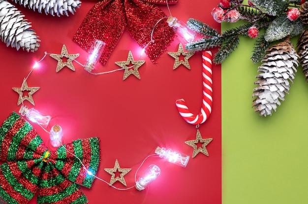 Sobre rojo navideño con espacio para texto sobre un fondo rojo y verde con dulces navideños y luces navideñas